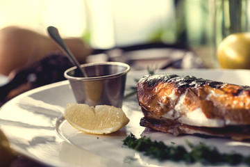 baked fish with rosemary, sauce and lemon on a wooden background