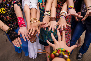 Many hands in bracelets with bright manicure
