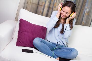Ragazza che ascolta musica sul divano