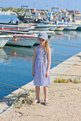 Little girl in the harbor in striped dress