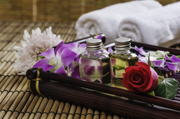 closeup of two essential oil, towel and flowers