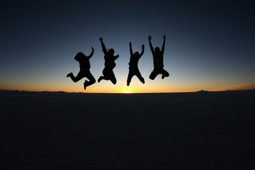 Happy friends jumping outdoor