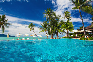 Infinity swimming pool on the beach with palm trees