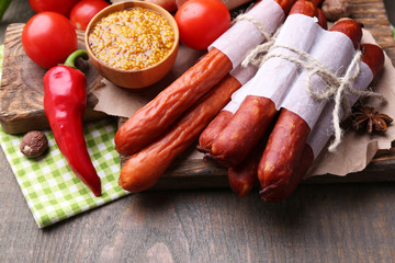 Assortment of thin sausages, mustard in bowl and spices