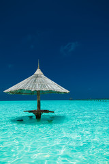Bamboo beach umbrella with bar seats in the water of an island