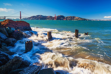 Surf splashes over rocks with the view of Golden Gate Bridge