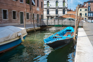 Narrow canal in Venice. Boats and reflection of colorful houses