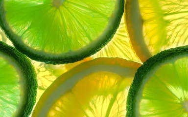 Lemon and green lime overlapped slices close-up background.