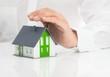 Immobilienberater hält seine Hand über Einfamilienhaus