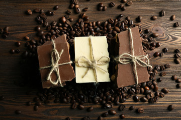 Stack of tied chocolate with coffee beans on wooden background