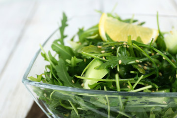 Glass bowl of green salad on wooden table, closeup