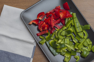 Sliced green and red peppers on a wooden table