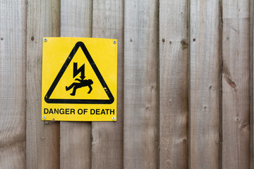 Caution Sign: Danger of Death on Wood background