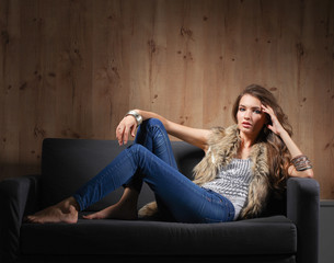 Portrait of elegant woman sitting on black sofa