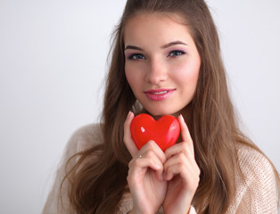 Portrait of beautiful happy woman holding a symbol heart.