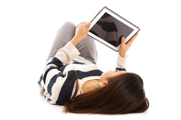 Smiling asian girl with tablet pc is lying on the floor over whi