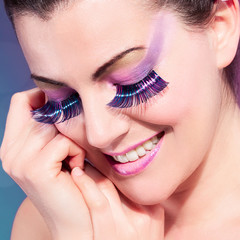Beauty closeup portrait of smiling woman with colorful eyelashes