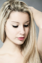Portrait of beautiful young blonde woman over gray background