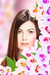 Portrait of brunette woman with orchids next to her face