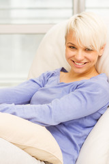 Blonde smiling woman is sitting on the sofa at home