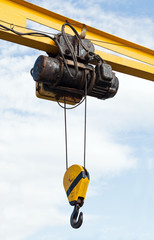 Beam crane with engine and hook hanging on ropes