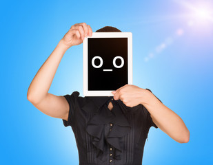 Young girl in black dress covered her face with tablet. On