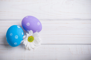 Easter colored eggs with flower on white wooden background