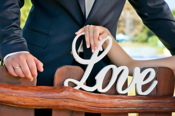 Newlyweds near the wooden bench show hands with rings.