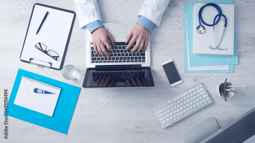 Doctor working at office desk - 81016494