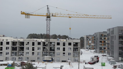 Winter construction site with cranes and workers building house