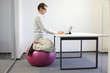 Man on stability ball working with tablet at desk