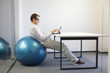 young man on stability ball at desk working  with tablet