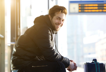Happy young man sitting with bag at train station