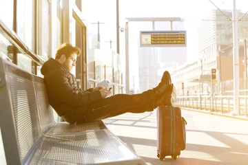 Young man waiting at train station platform with mobile phone