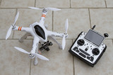 A quadcopter with camera gimbal system and radio transmitter poster