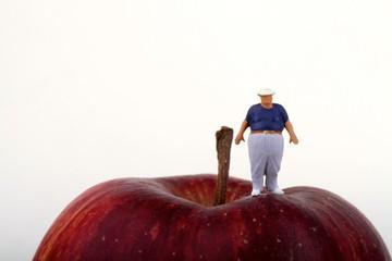 miniatura di uomo obeso su una mela rossa
