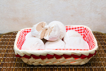 Marshmallows in a wicker basket on a bamboo tray