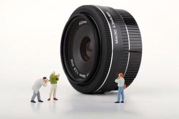 miniature di fotografi davanti ad un obiettivo fotografico