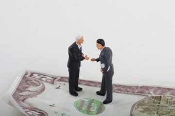 miniature di uomini d'affari che trattano su una banconota