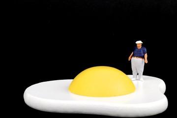 miniatura di uomo obeso ed uovo fritto