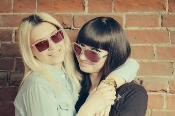 Two girls hugs having fun, wearing sunglasses