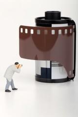 miniatura di fotografo davanti ad un rullino fotografico