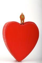 miniatura di uomo solitario sopra un cuore rosso