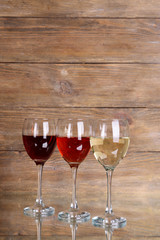 Different glasses of wine on table on wooden background