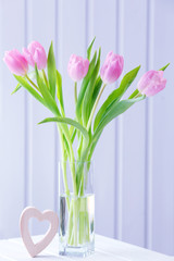 Beautiful pink tulips with decorative heart on wooden