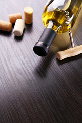 Bottle of wine with corks and corkscrew on wooden background
