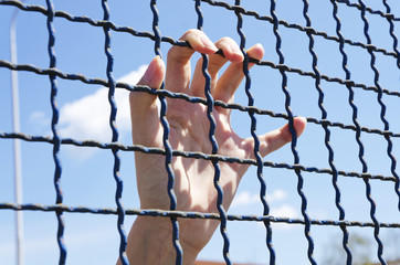 hand grasping a metal fence