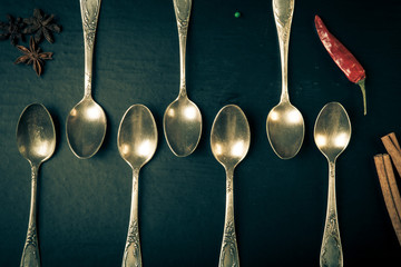 Herbs and spices with old metal spoons on a black background. To