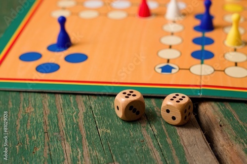 Two wooden dices in front of ludo with figurines - 81029028