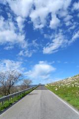 Strada asfaltata con nuvole nel cielo azzurro